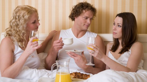 two girls with one guy having breakfast in the bed